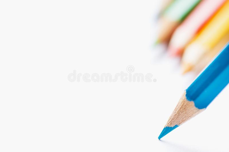 Row of Multicolored Pencils in Background Single Blue Sharp Pencil Pointing with Tip to Blank White Paper. Beginning of Drawing stock images