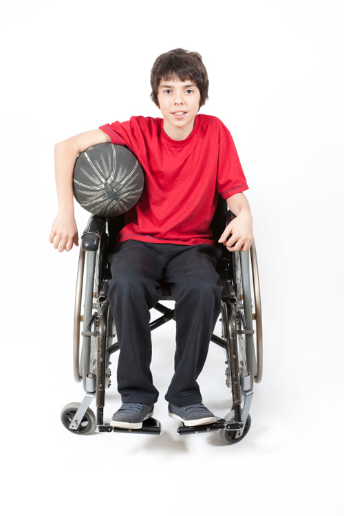 A boy in a wheelchair holding a basketball.